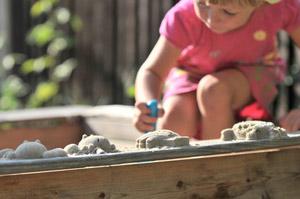 Mädchen backt Kuchen im Sandkasten